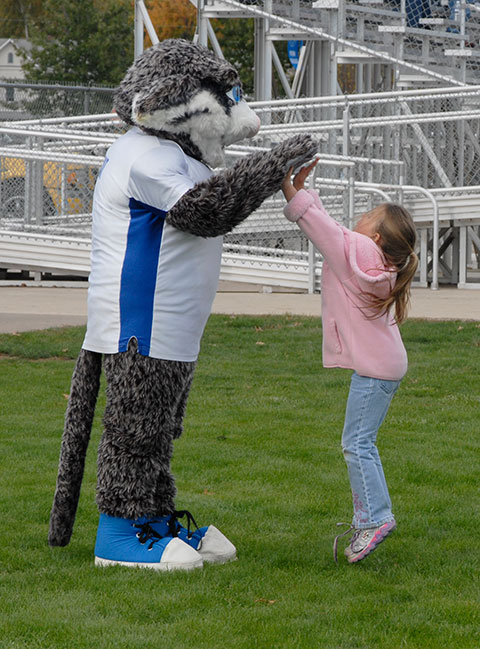 The Wildcat makes a soccer-field friend with a very high five (or two).