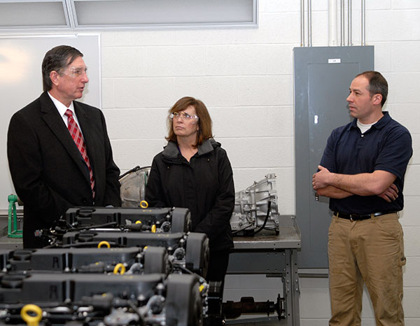 Automotive instructor Christopher A. Trapani, right, and the Balogas stand amid some of the 12 General Motors engines donated through The Pennsylvania State University.