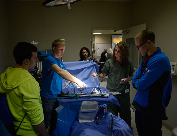 Shedding some light on surgical technology, with the help of 2012 alumna Jaime L. Binkley (background)