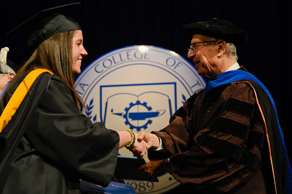 Board of Directors Chairman Robert A. Secor offers his encouragement to a new graduate.