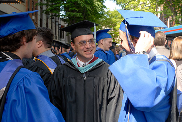 Christopher H. Van Stavoren, an assistant professor of automotive technology (center), reconnects with students after Friday's ceremony.