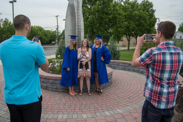 Friends help early childhood education graduates Kirstie A. Swisher (left), and Kelsey A. McGarry preserve a memory in the college's Remembrance Garden.