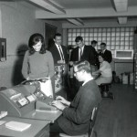 Members of the second graduating class of data-processing students practice on the college's first computer, an IBM 1620 (mainly hidden in the background), in the college's first computer lab, in Unit 6, in 1967.