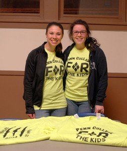 "Photographed during a recent THON ""Gold Out"" benefit in Bardo Gym, Kelsey J. Maneval (left) and Madeline A. Lusk sell (and wear) the charity's T-shirts, while putting a friendly face to the serious battle against pediatric cancer."