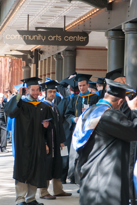 Under the Arts Center marquee, graduates check their tassels one last time before entering.