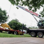 A commemorative heavy-construction blade is lifted off the truck ...
