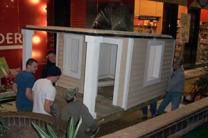 Manuevering the miniature house into place at the Lycoming Mall, are counterclockwise from upper left, Construction Management Association members Thomasz Jezowski (dark blue sweatshirt), Justin J. Kovaleski, James P. Craft, Nicholas L. Fragello and Ryan P. Becker (grey sweatshirt).