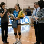 Women's volleyball coach Bambi A. Hawkins joins senior Tara M. Powell and the honoree's parents at midcourt.
