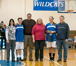 Lady Wildcats Kierstin Steer (second from left) and Mackenzie Brown join their parents at midcourt for Senior Day recognition.