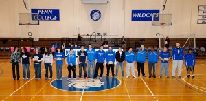 Fall championship sports teams gather at midcourt for postseason recognition.