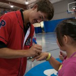... and Drew Anderson autographs a girl's hand.