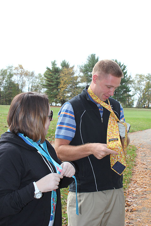 "Valerie L. Fessler, director of alumni relations/annual giving, coaches Casey A. Poeth through some necktie ""issues."""