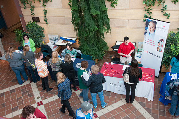 Students talk with recruiters from a variety of health care organizations in the ATHS lobby.