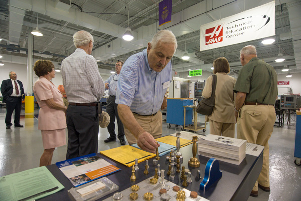 Edmond A. Watters III, who served as dean for degree and certificate programs from 1978-81, investigates creations in the manufacturing technology lab.