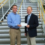 Brian M. Fuhrman, left, major account manager for Waste Management Inc., delivers a donation to Robb Dietrich, executive director of the Penn College Foundation.