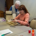 Amanda McCavour (seated) provides artistic assistance to workshop participant Sally Ickes, of Danville.