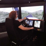 Pamela Mix, secretary to the ESC executive director and assistant dean of transportation and natural resources technologies, takes the wheel of the simulator.