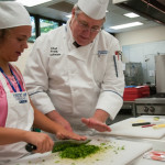 Chef Frank M. Suchwala, assistant professor of hospitality management/culinary arts, helps a student learn knife skills as she minces parsley.