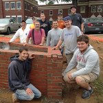 "A ""Penn College 2015"" brick signifies the workmanship by instructor Glenn R. Luse (in suspenders) and nine students from his Advanced Masonry class, who constructed accessible flower beds at the Lysock View Complex."