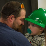 Meredith places a hard hat on his son, one of seven family members to share in the success of Meredith and his brother.