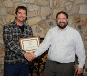 Chris S. Weaver (left), an instructor of diesel equipment technology at Penn College, accepts a plaque and congratulations from past recipient Justin W. Beishline, assistant dean of transportation and natural resources technologies.
