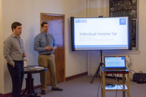 Penn College accounting faculty members Michael D. Shipman (left) and Bob Nolan offer guidance on income tax return preparation at a Thrive International Programs event, held at City Alliance Church in Williamsport.