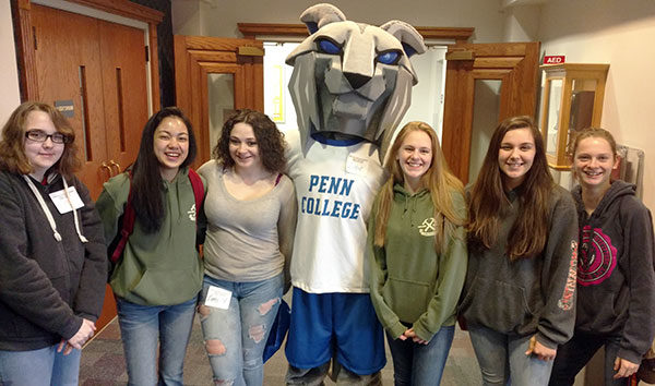 A half-dozen high school students hobnob with the Wildcat outside the ACC Auditorium.