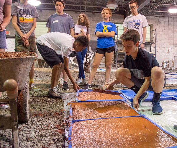 Led by Franklin H. Reber, instructor of building construction technology, and students, Career Day visitors create concrete stepping stones.