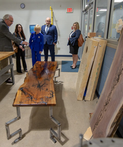 In the college's makerspace, Tom Gregory, associate vice president for instruction, points out a student's handcrafted live-edge walnut wood table, featuring artistic touches achieved with wires and electric arcs. The table is the handiwork of Michael C. Aja, of Novi, Mich., enrolled in welding and fabrication engineering technology.