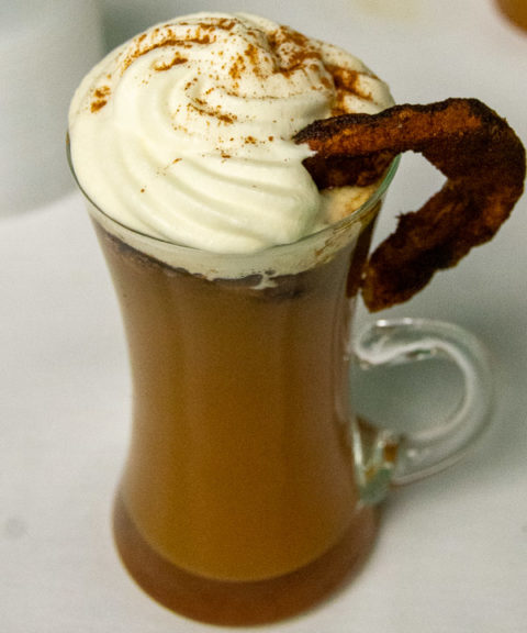 """The People's Choice Award-winning mocktail, """"Spike-Less Hot Cider,"""" concocted by Linde and Showers, is served with a baked apple slice and whipped cream."""