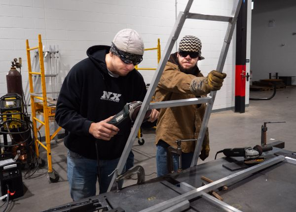 Welding students Nolan Durecki (left) and Christian A. Novick assist with grinding edges of the A Wall.