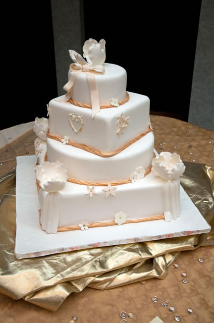 Peach cabbage roses and gold braids adorn a cake.