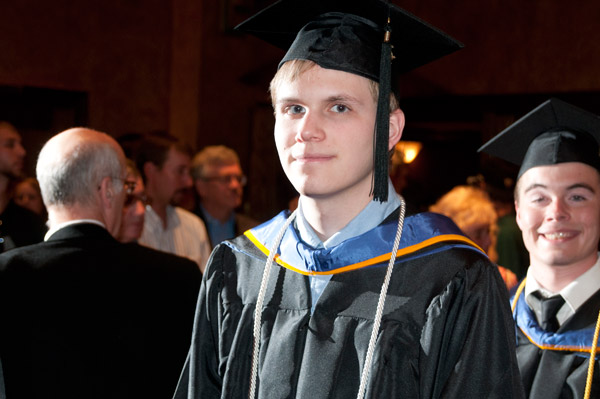 Newly minted graduates pass crowds of well-wishers as they leave the Community Arts Center.