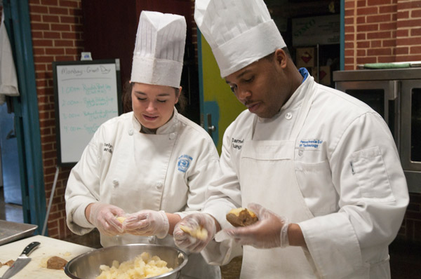 Katelyn R. Ciavardini and Darnell R. Bungy, both seniors in the culinary arts and systems major, prepare potatoes for a baked potato soup demonstration by Kathy Wickert, chef at Giant Super Food Store Cooking School.
