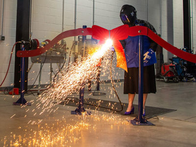 Pennsylvania College of Technology President Davie Jane Gilmour deftly wields a plasma cutter to sever a metal ribbon during a dedication ceremony for a greatly expanded welding facility at the college.