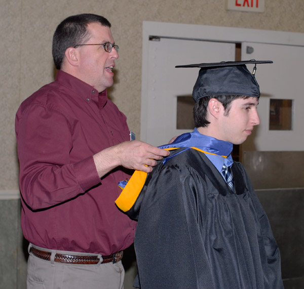 Multitasking Matt P. Branca, college store director, fixes a student's hood and instructs another soon-to-be graduate nearby.